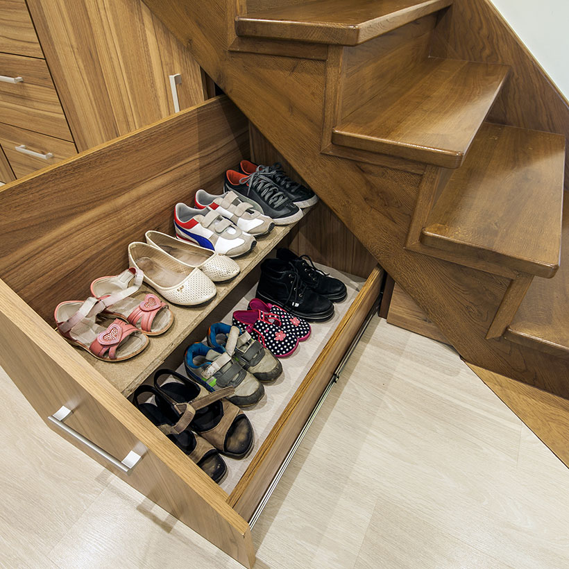 Under stairs storage pull out drawer works really well to store shoes and accessories