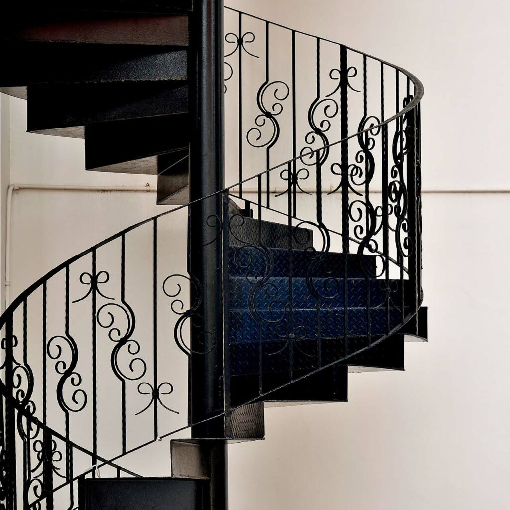 Spiral staircase design with a delicate wrought iron railing is beautiful to look for indian homes staircase design