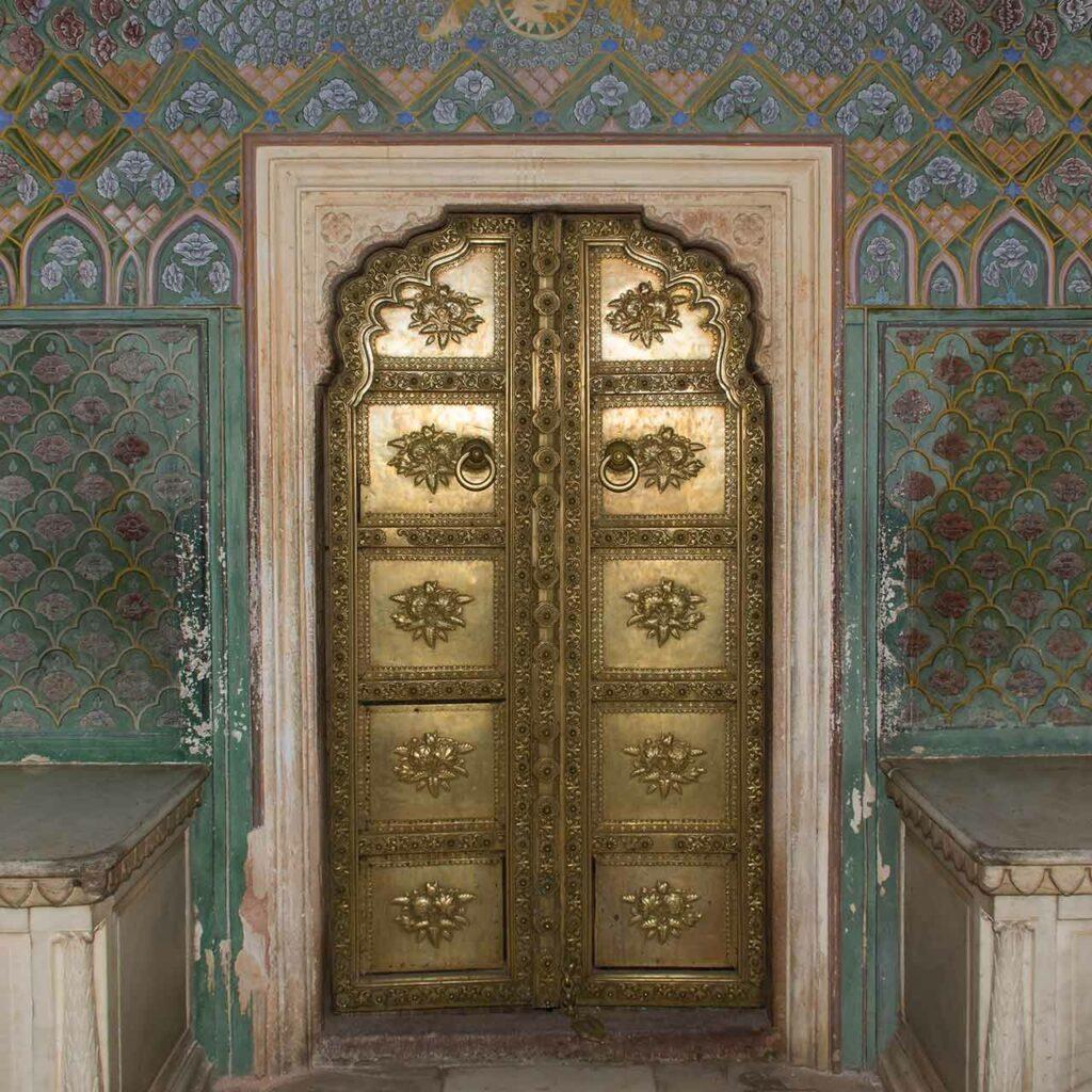 Antique pooja room door design in wood with metal work and gold plated