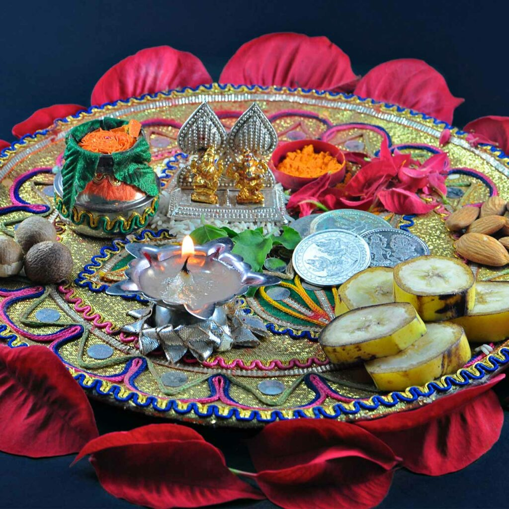 A colourful pooja thali adorned with miniature idols and a single diya is one of the popular Diwali pooja thali decoration ideas.