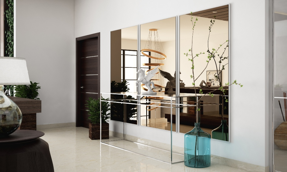 Simple drawing room designs in India showing drawing room wall design and decoration using mirrors and side tables to bring contemporary look.
