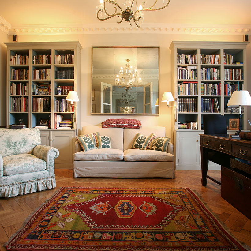 Indian Living room ideas with big sofas and lamps on both sides with a large mirror in between and big book shelves on both sides for Living room colours