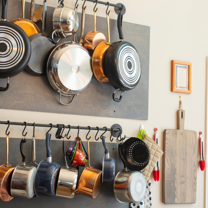 Kitchen organisation tips to store all the pans at one place by hanging them on the wall on a horizontal rod for kitchen organization