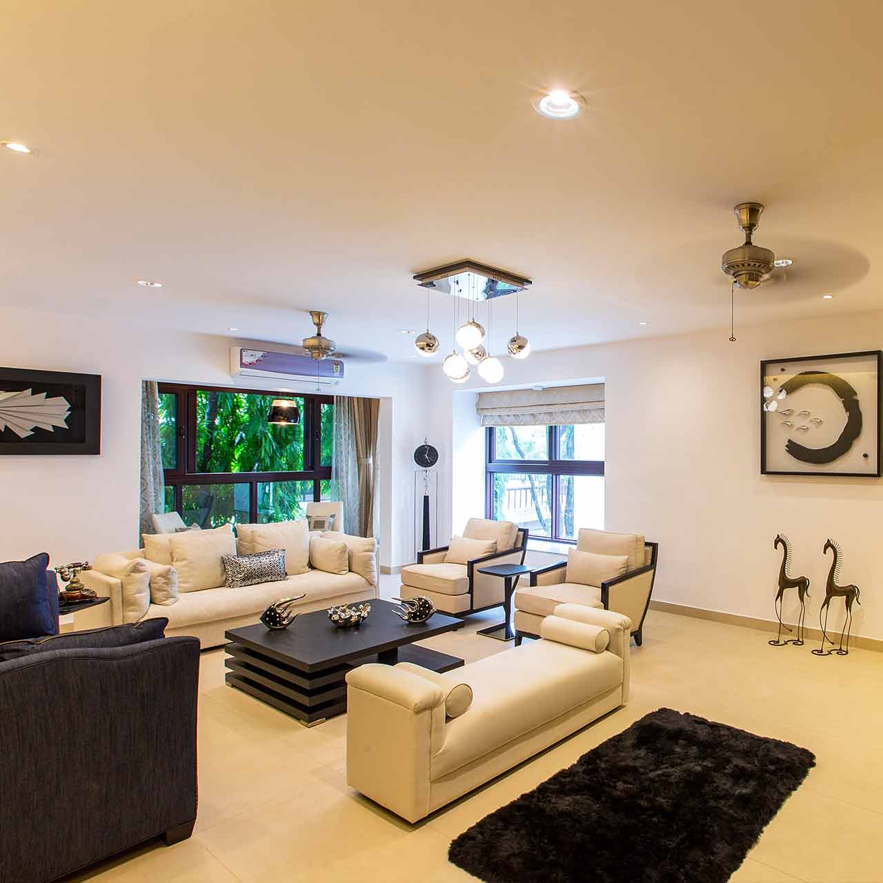 Traditional style living room design with elegant furnishing, textured rugs, bright statement lighting, and bright colour schemes