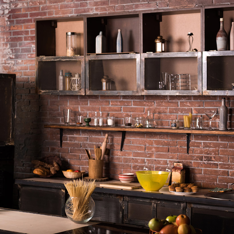 Traditional indian kitchen design gives galley area a traditional indian touch and use red brick walls as backsplashes
