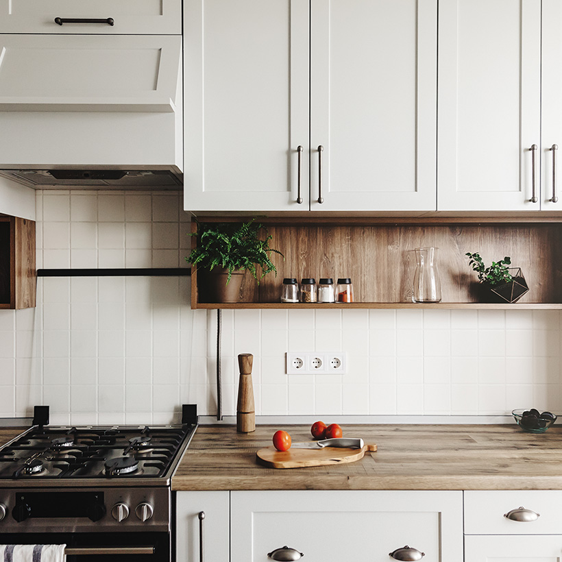 Simple indian kitchen design with a modern classic combination of white cabinetry and wooden countertops