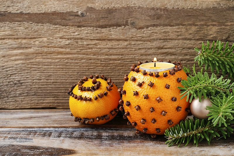 Homemade christmas diy idea to enhance your decor using oranges garnished with cloves to make tea light candle stand.