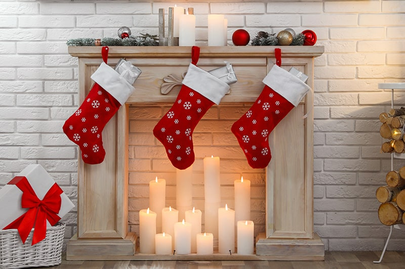 Decorate your fireplace with simple and easy christmas home décor ideas like placing candles, ribbons.
