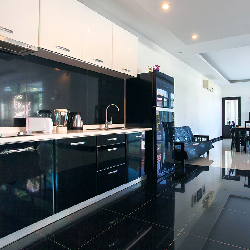 Modular kitchen cabinets with glossy finish of drawers of black in colour and white on the top in corner kitchen cabinet