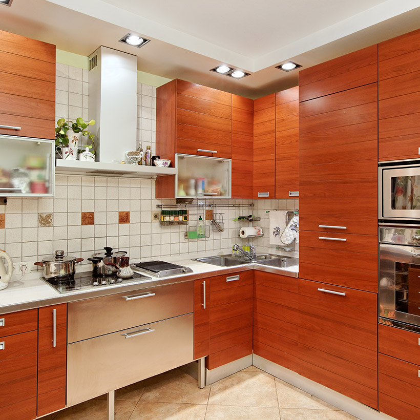 Corner kitchen cabinet with wooden finish with steel chimney and drawers in kitchen cabinet design for small kitchen