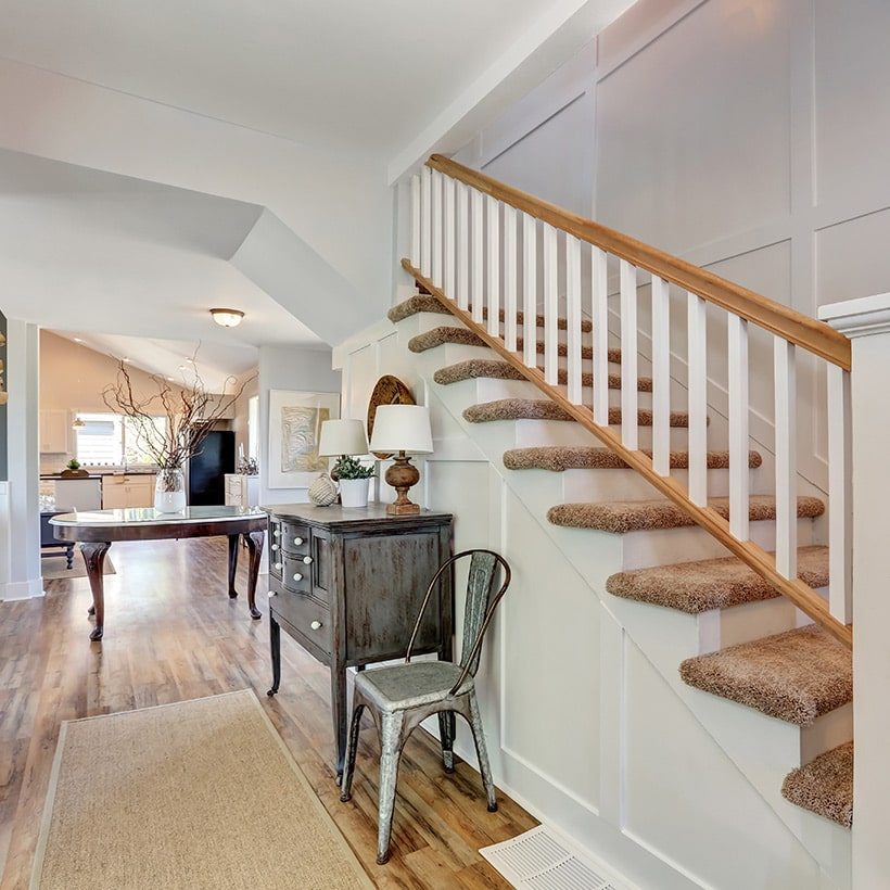 Small entryway with stairs decorated using foyer table, wall decor, arch design, door design.