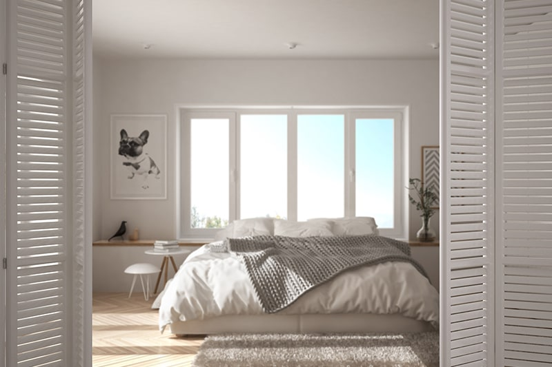 Wooden door design for bedroom with white louvred doors fold back to reveal a pristine bedroom
