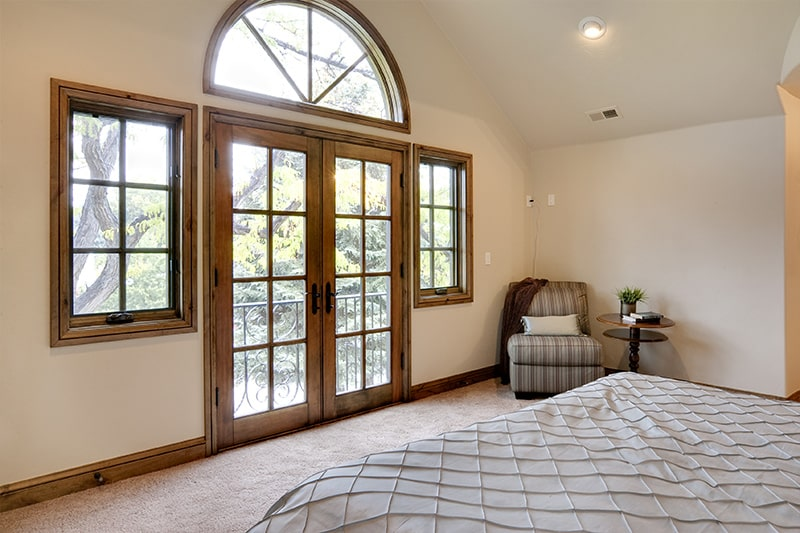 Master bedroom design with french doors having glass windows extending the whole frame