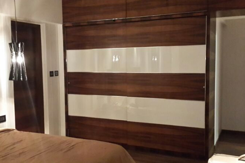 Modern wooden wardrobe designs for bedroom made up of heavy wood covering the whole wall