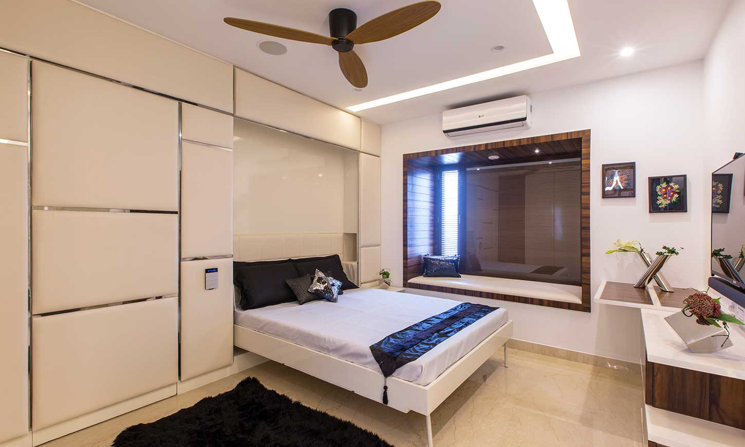 A guest bedroom designed by interior design studios in bangalore with an invisible murphy bed which saves space