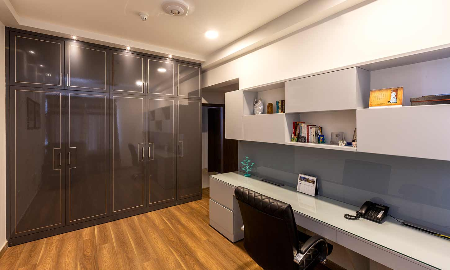 house interior design in bangalore with a grey and white theme for home office with a glossy wardrobe