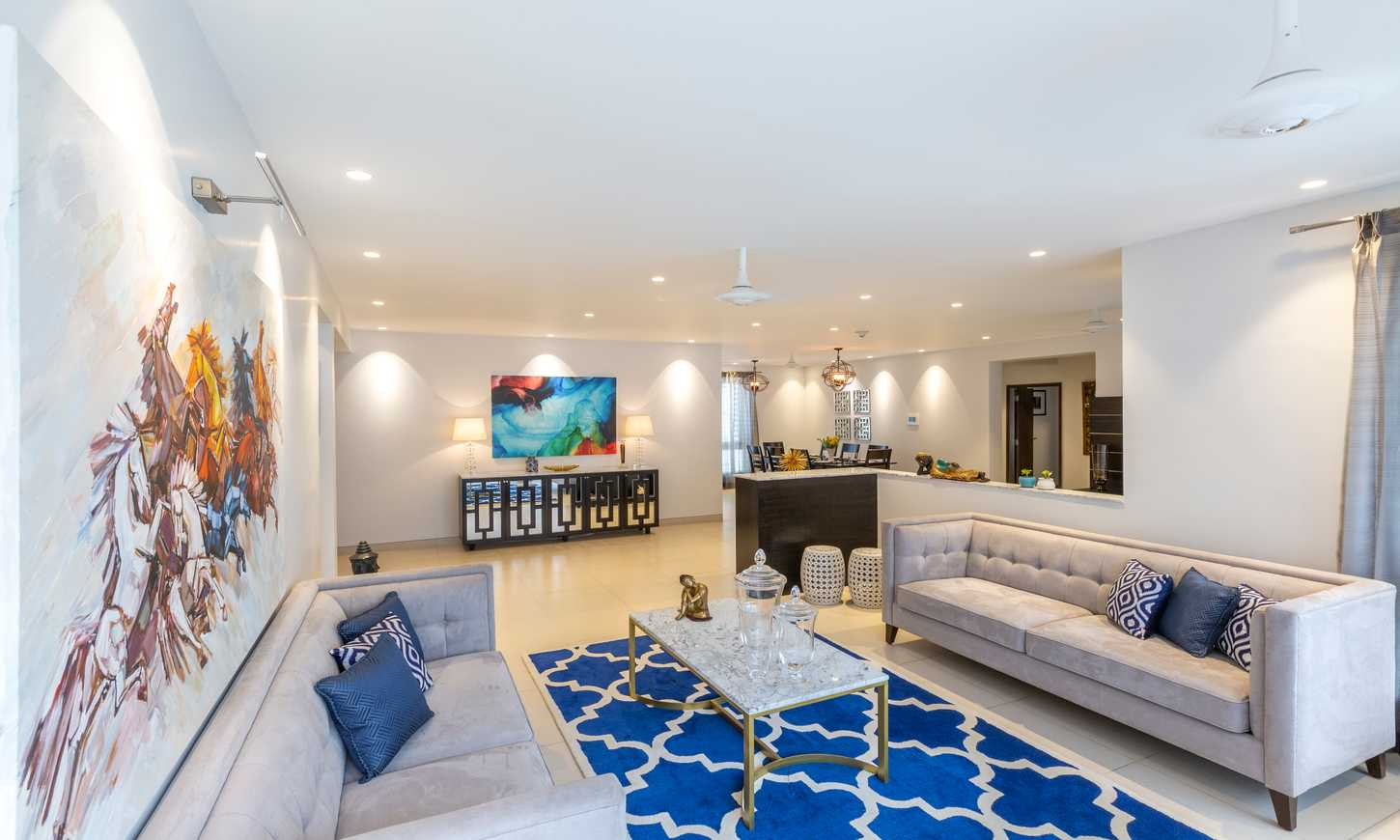 A modern living room with sofas and royal blue carpet by luxury interior designers in bangalore