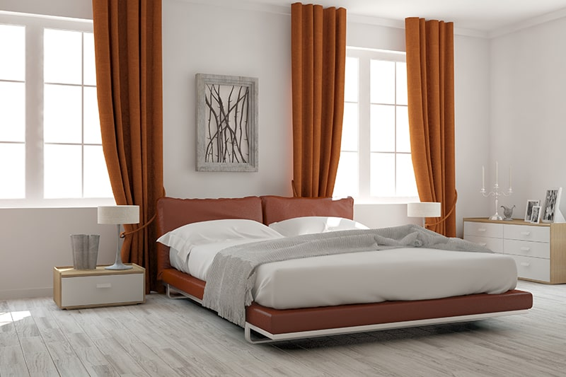 Bedroom designs india with a low lying bed frame against a pop of tangerine