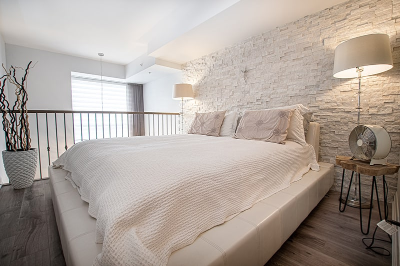 Bedroom designs india with low cost by using combination of wooden flooring and brick walls