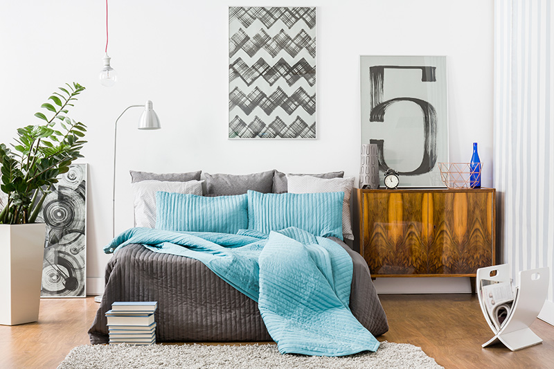 Grey and white accents with frames complementing groovy decor of a modern bedroom