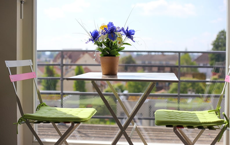 Outdoor balcony furniture design with light, eye soothing colours like brown, greens, whites