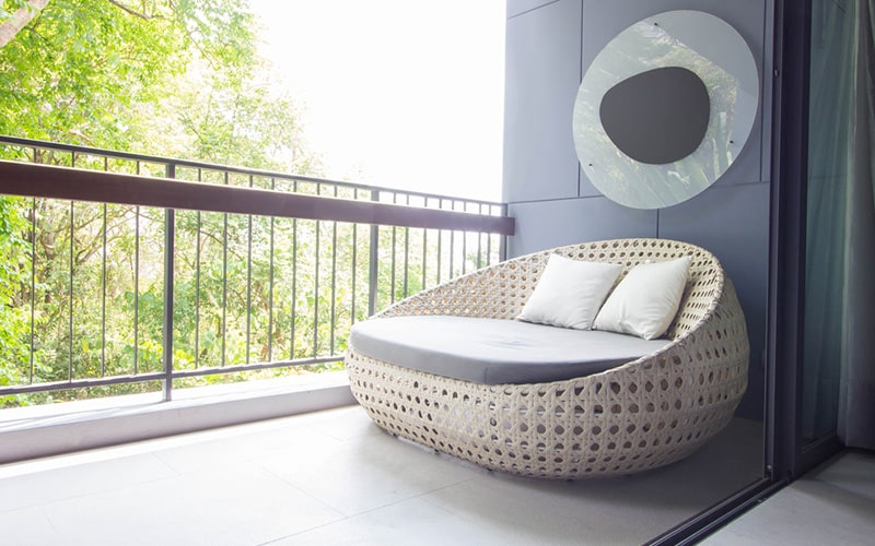 Space saving outdoor balcony furniture with cane chair and a wall hanging for small space balcony