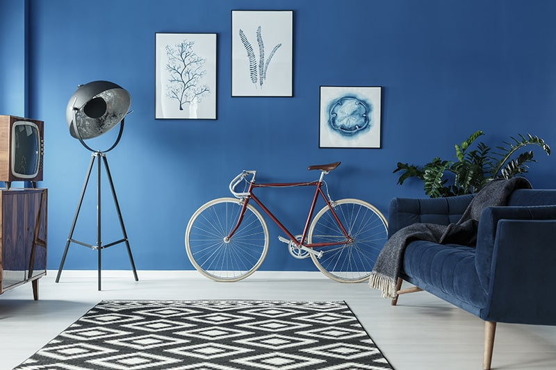Ocean blue wall paint colors with modern art frames and a black and white patterned carpet to your living room blue house colors