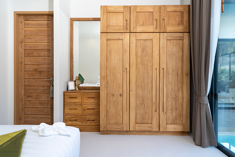 Traditional wooden door wardrobe gives a rustic look to the bedroom interiors