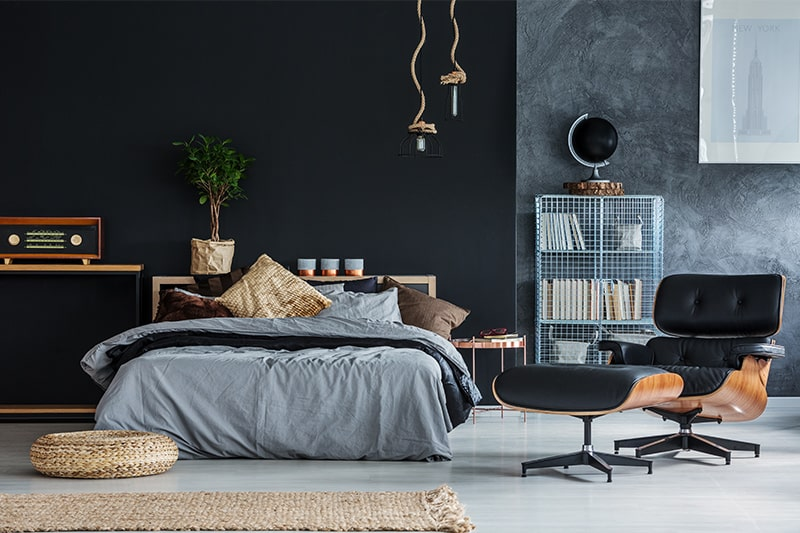 Black bedroom furniture with colourful accent chairs and knick-knacks elevate
