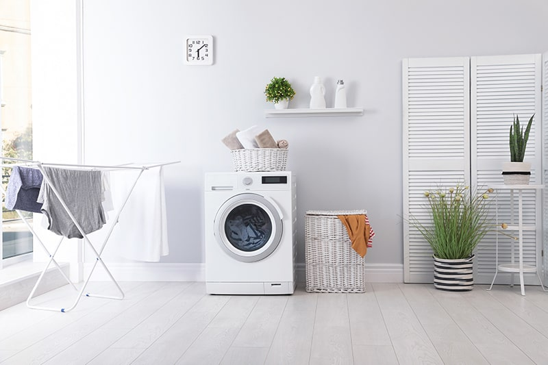 Design your laundry room walls, floors, washing machine, storage units, pots, clocks are all white