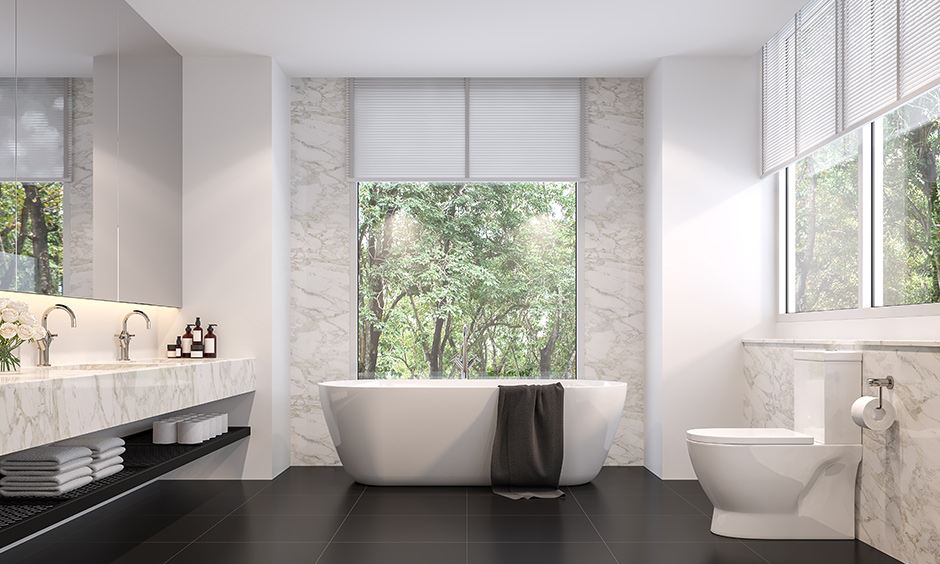 Black floor tiles in a bathroom which is designed with a simple dual shade look