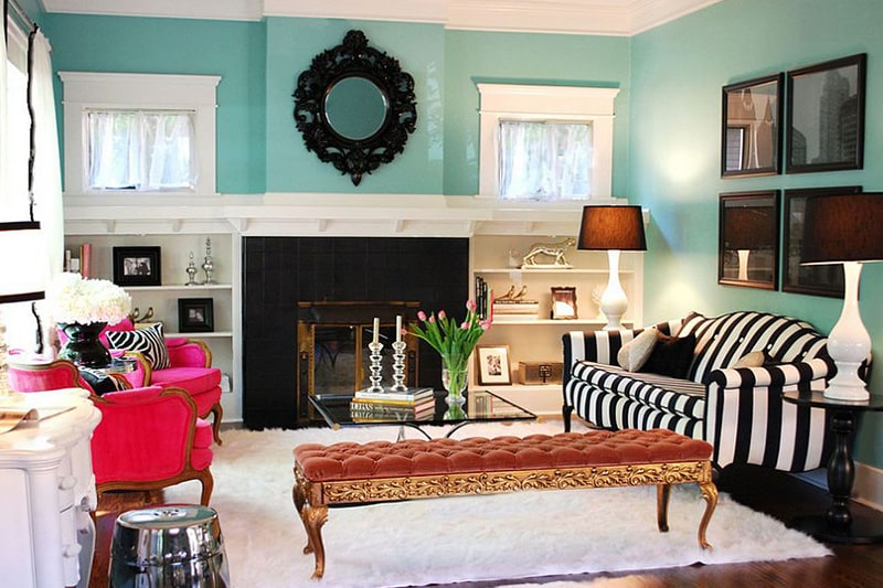 A tiffany blue living room walls with a pair of hot pink armchairs
