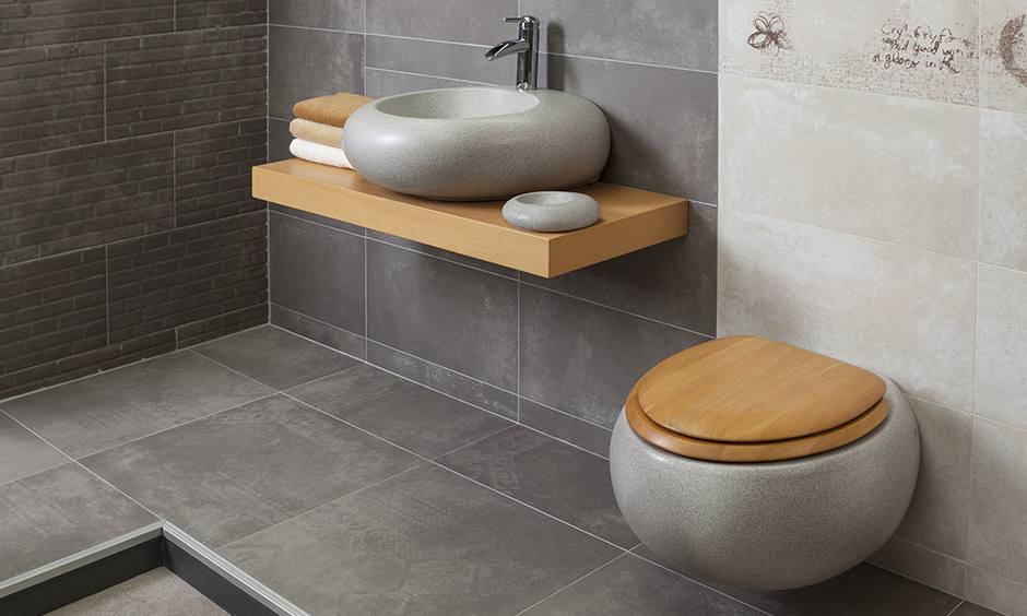 Designer bathroom sink basins made with granite and carefully crafted in a round-shape fitted on a wooden floating countertop