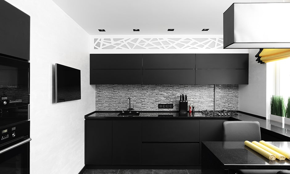 Ultra modern black and white kitchen with black cabinetry and white walls