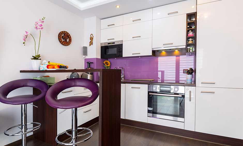 Small space modern kitchen design where fits in a personalised dining table and purple chair looks stunning.