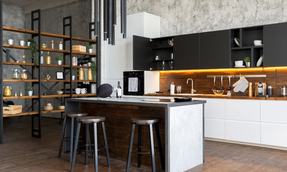 Industrial kitchen with a bold steel chair, cylindrical chandelier and pitch black top cabinets steals the show.