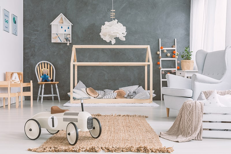 Decorate your kids room with scandinavian style by adding small-height wooden bed and a large arm chair