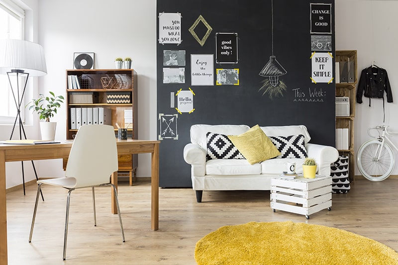 Small living plus study room decor with a wooden desk and chalkboard wall with inspiring quotes for your home