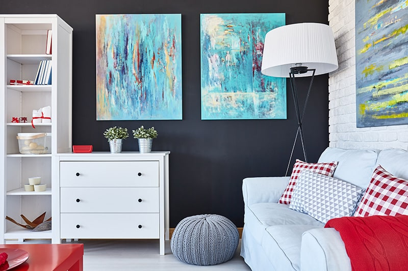 Living room decor with blue-shaded sofa, cabinet and blue abstract paintings on wall gives contemporary style in your home