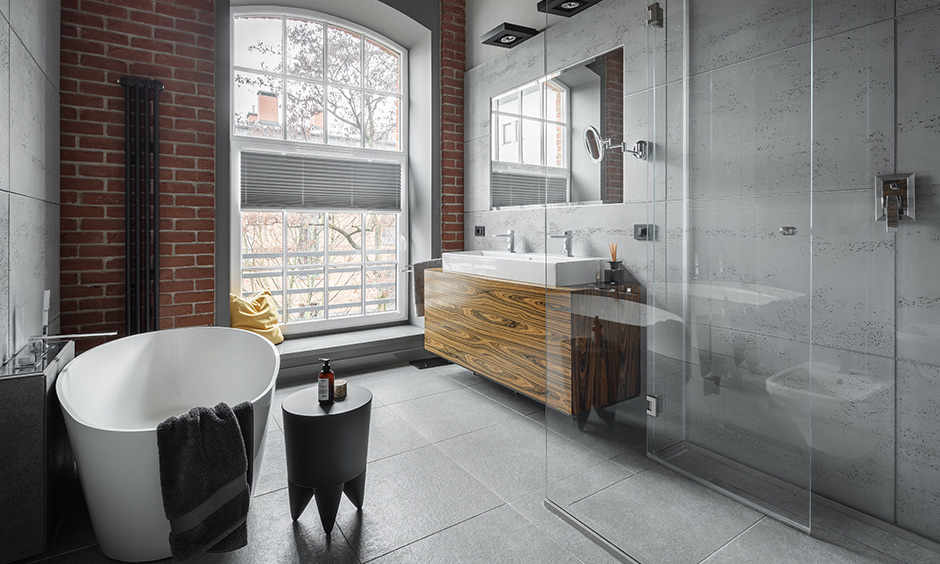 Industrial design with exposed bricks, concrete, iron beams, and factory pipes are master bathroom design ideas.