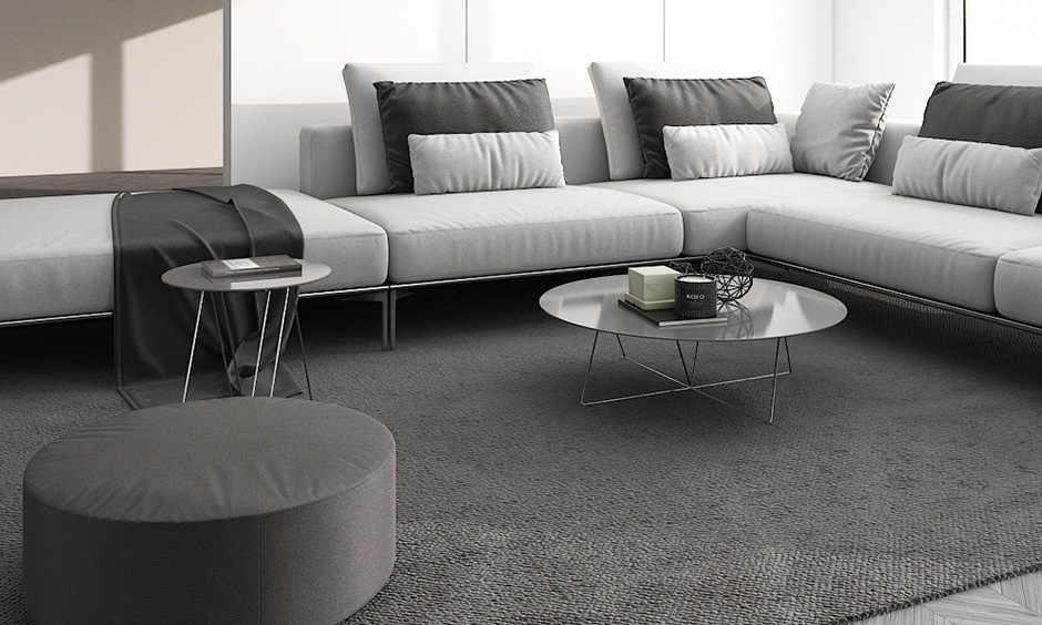 minimalist living room india with sofa set, monochrome pillows and a glass coffee table