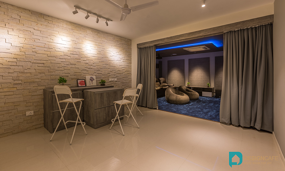 Interior design villa style for a basement in the luxury villa to create an entertainment area with portable bar and chairs. Adarsh Palm Retreat Club House.