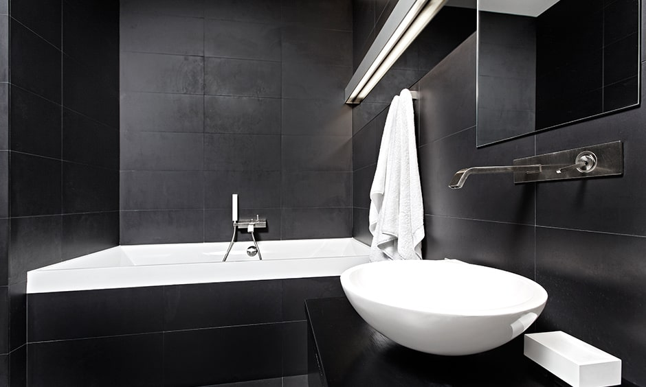 Classic black and white bathroom design black walls and floor and contrasted by the white bathtub