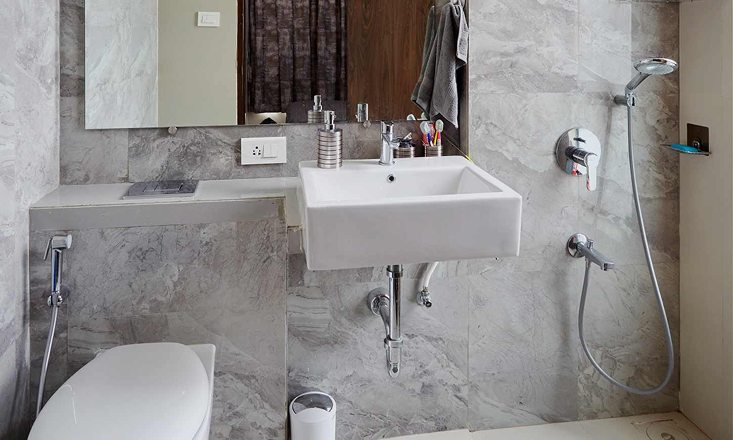 Bathroom design with grey tiles designed by interior design company in mumbai