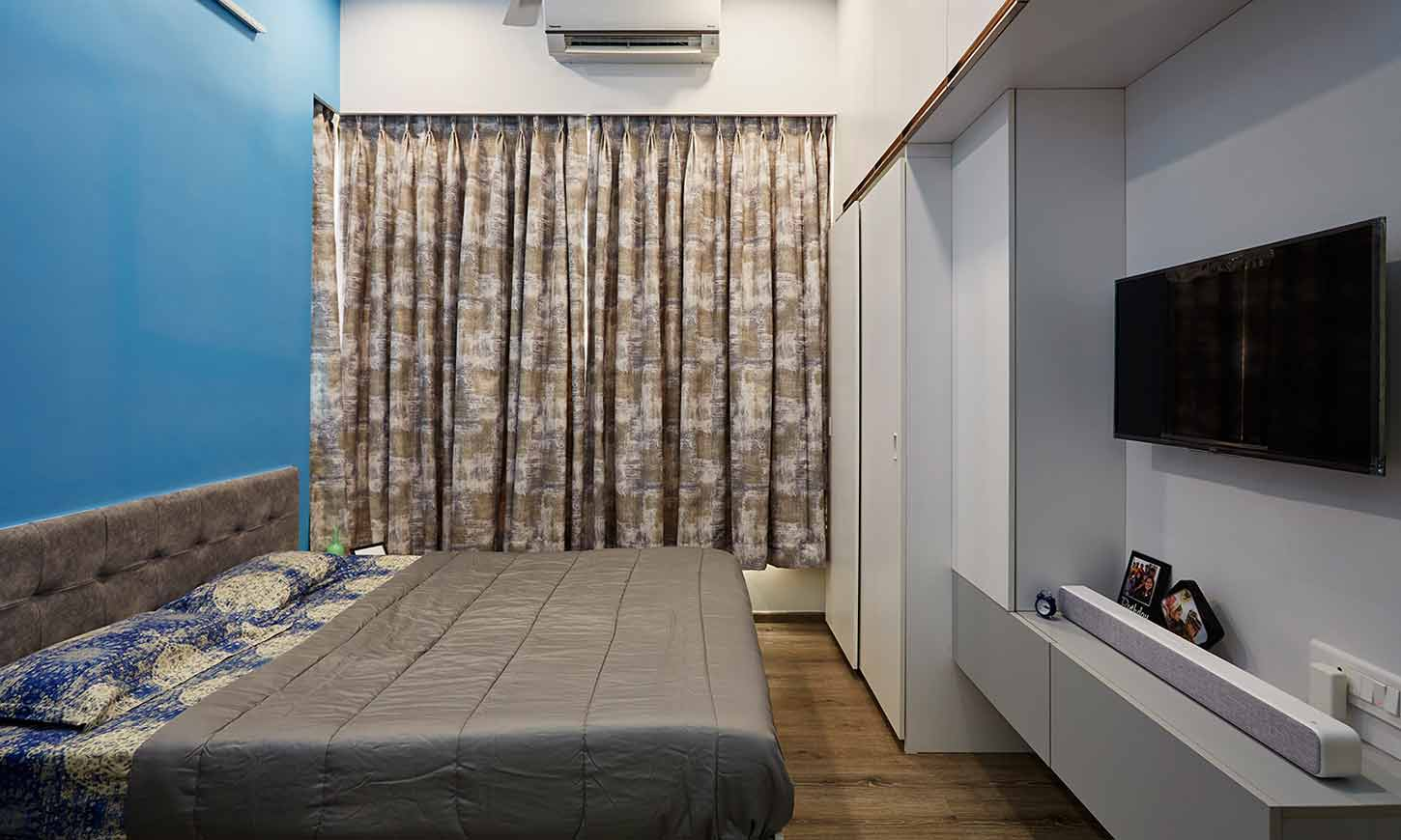 Bedroom designer in mumbai with wall mounted bedroom cupboards and a tv unit