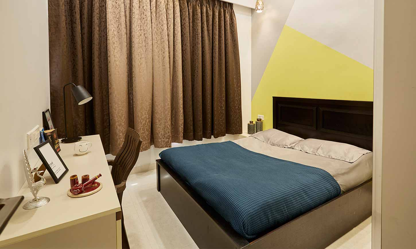 Bedroom interior design in mumbai with a working table and brown curtains