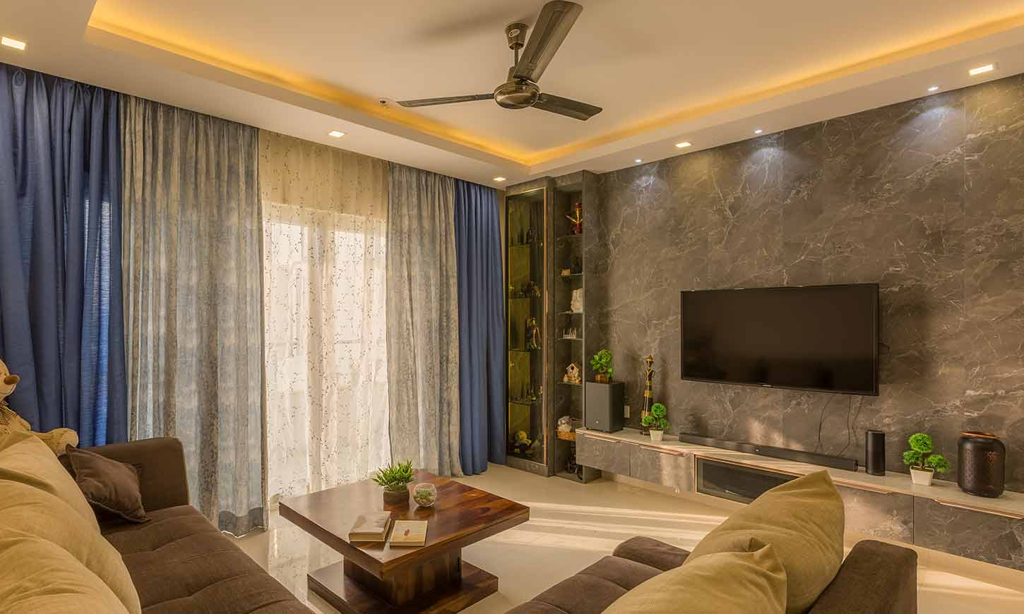 Living room interior design bangalore with a tv unit designed by home interior designers in bangalore
