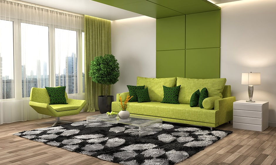 A floor to ceiling green panel and green patterned cushions to your living room interior design