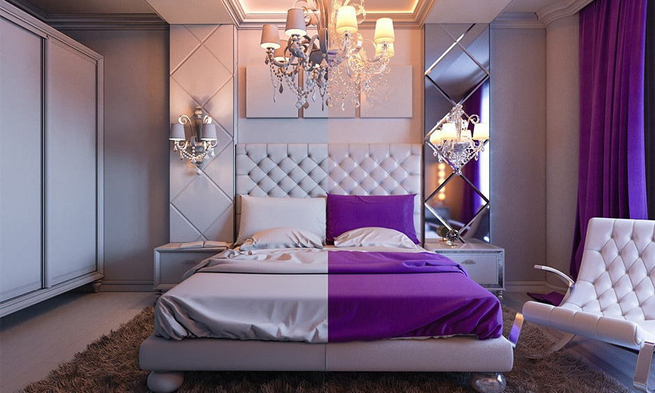 Modern purple bedroom decor with a chandeliers and comfortable white velvet armchair
