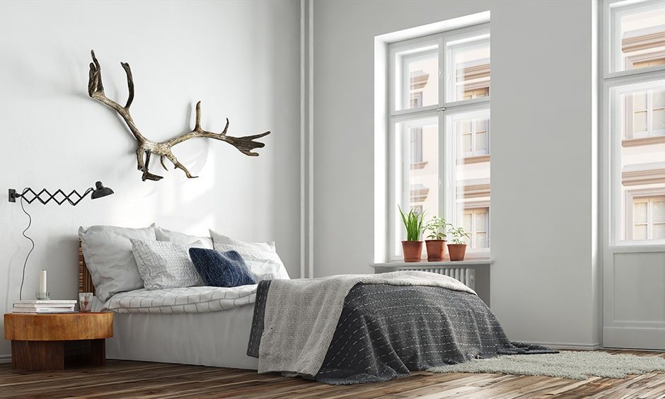 Modern minimalist bedroom interior design with a few potted plants on the window sill